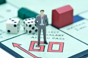 London, UK - July 2, 2011: Model figurine of a businesman at the starting point of the board game monopoly Stock photo description Model figurine of a businesman at the starting point GO of the board game monopoly with hotels and dice in the background